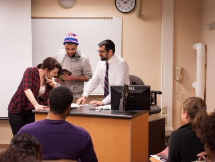 Students working with a professor in class